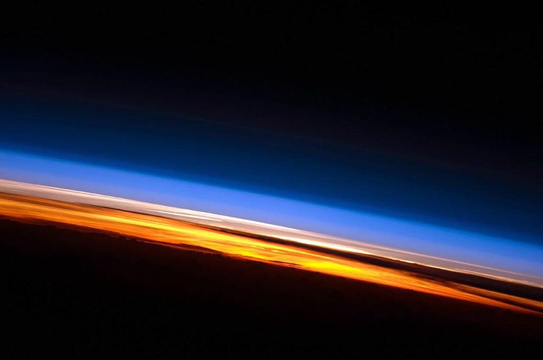 Solnedgang fotografert av en satellitt over Det indiske hav. Her ser du tydelig lagene i atmosfæren. Nederst i oransje og rødt er troposfæren. Over der ligger stratosfæren i rosa og hvitt. Over den forsvinner gradvis resten av atmosfæren (blå) ut i verdensrommet. Avstanden fra jordoverflaten til toppen av stratosfæren er i underkant av 1 prosent av jordas radius.