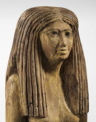 Trestatue av egyptisk kvinne, 1900–1800 f.Kr. Hun har en stor parykk, satt som brede lokker. Ved midtskillen ser vi en liten strek som viser et tørkle under parykken.