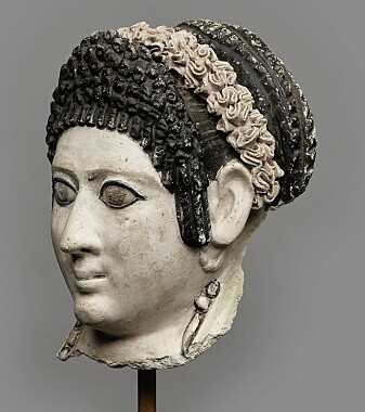 Kvinnehode fra det romerske Egypt, 1. årh. e.Kr. Hodet har sittet på en mumiekiste. Kvinnens frisyre er inspirert av moten blant kvinnene i den flaviske keiserfamilien. Luggen høyt oppsatt med krøller, det lange håret sirlig flettet og bundet i en stor knute. Som hårpynt har hun en krans i rosa farge.