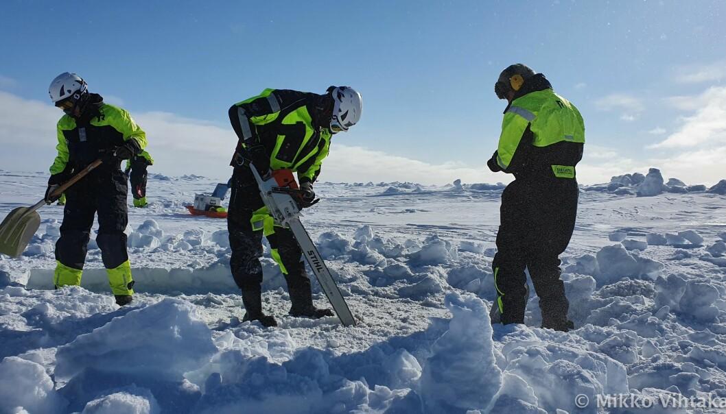 """Amalia, Peter and Håkon lager et dykkehull i den 1,5 tykke isen i kaldt vintervær. På Svalbard så blir været målt i hva en trenger å ha på seg den dagen. Denne dagen var det en """"Balaclavadag"""""""