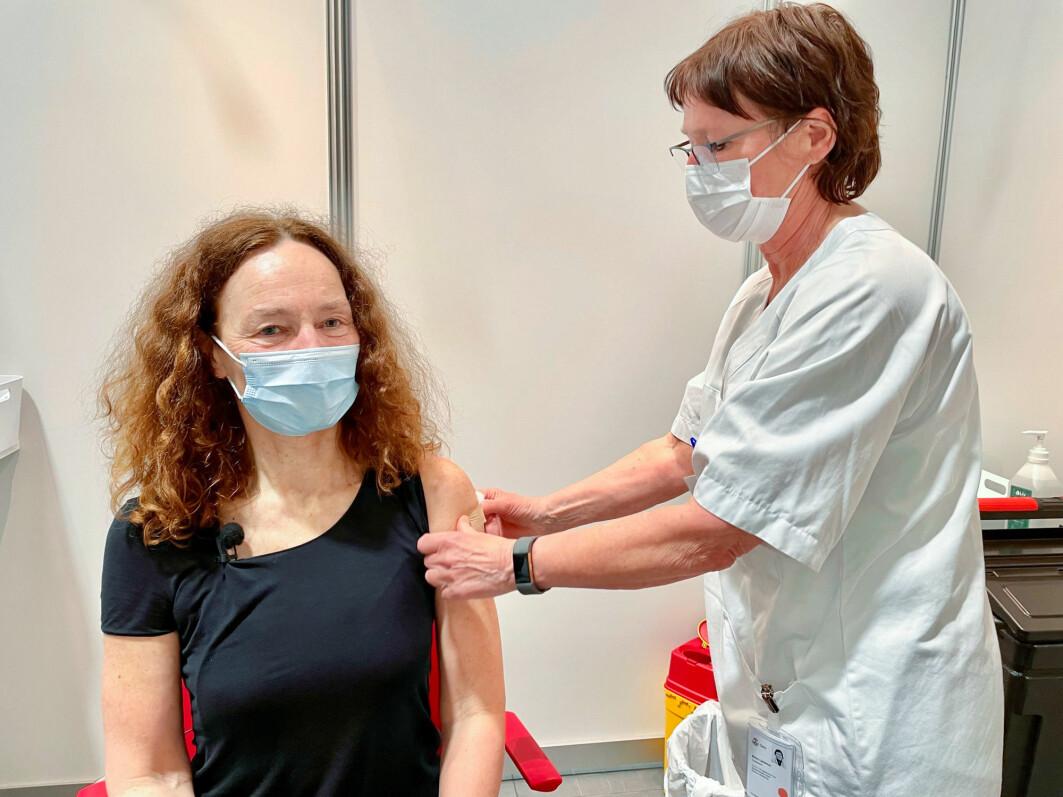 Sykepleier Ellen Lødemel setter plaster på stikket, etter at direktør i Folkehelseinstituttet, Camilla Stoltenberg, ble vaksinert mot covid-19 i mai i år.