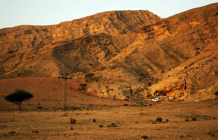 Arkeologer har funnet 120 000 år gamle spor av mennesker ved Jebel Faya i De forente arabiske emirater. Steinalderboplassen ligger rett bak den hvite bilen i bildet. (Foto: Science/AAAS)