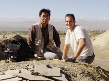 """""""Paleontologene Hai-lu You (t.v) Matthew Lamanna i nærheten av funnstedet i Changma. Flere fossiler er synlige i forgrunnen. Photo: Kenneth J. Lacovara/Drexel University."""""""