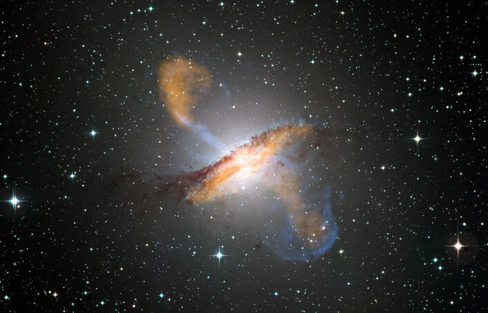 Bildet viser jetstrømmene som kommer ut av det sorte hullet midt i galaksen Centaurus A. Bildet er satt sammen av tre bilder; ett tatt av synlig lys, ett av mikrobølger og ett av røntgenstråler. (Foto: ESO/WFI (synlig lys); MPIfR/ESO/APEX/A.Weiss et al. (mikrobølger); NASA/CXC/CfA/R.Kraft et al. (røntgen))