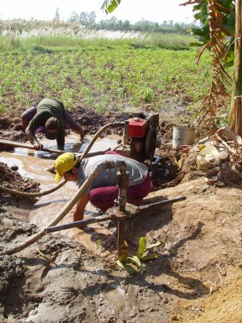 To kambodsjanere arbeider med en brønn som skal gi drikkevann. (Foto: Shawn Benner)