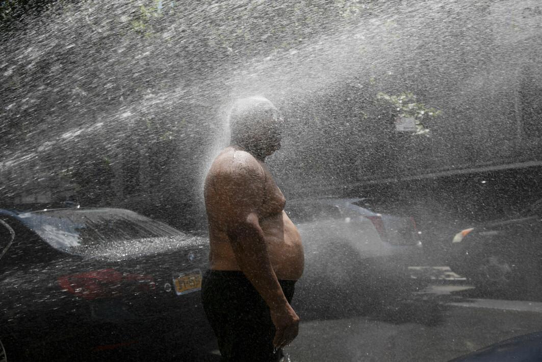 Denne mannen kjølte seg ned med vann fra en brannhydrant under en hetebølge i New York i fjor. Mange varmerelaterte dødsfall kommer som en følge av global oppvarming.