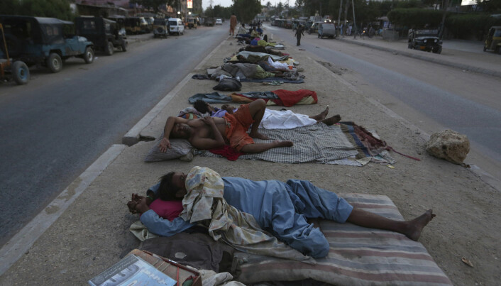 Arbeidere hviler på bakken i Karachi i Pakistan 18. mai da deler av Pakistan opplevde en hetebølge.