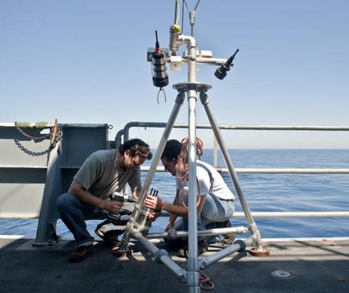 Timothy Crone (t.v.) forbereder et undervannskamera som skal brukes til å studere hydrotermale kilder utenfor nordvestkysten av USA. Han brukte en tilsvarende metode for å beregne utslippene fra Deepwater Horizon-katastrofen. (Foto: Carlos Sanchez, OOI-RSN Enlighten'10 Cruise, University of Washington)