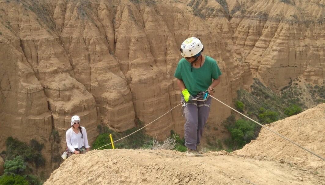 Fjellsidene i bakgrunnen er bygget opp lagvis med jord, sand og støv gjennom millioner av år. De ulike lagene er litt forskjellige fra hverandre. Det bruker forskerne til å forstå ulike tidsperioder bedre.