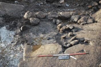 Her ses rester av brannlaget med kantstein intakt. Fotsålene skimtes i forgrunnen. (Foto: Anne Haug/ NTNU Vitenskapsmuseet)