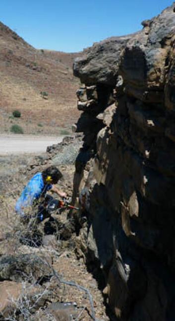 Morgan Ganerød fra NGU borer seg inn i bergveggen for å ta prøver.