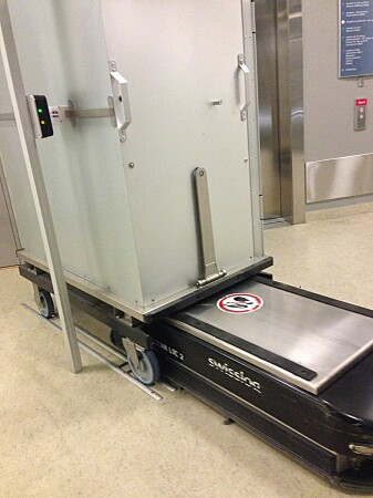 St. Olavs Hospital was the first hospital in Scandinavia to adopt the use of simple transport robots in the hospital buildings. The photo shows one of the robots loading a cart.