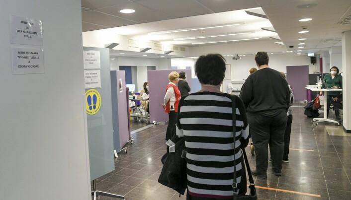 Pasienter står i kø for å få koronavaksinen på et vaksinesenter i Vantaa i Finland i mars.