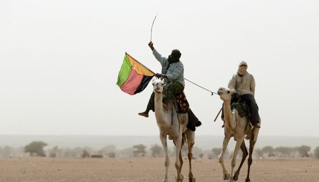 Azawad ble utropt som egen stat i den nordlige delen av Mali i 2013 – her holder en støttespiller flagget til staten under en demonstrasjon. Lokale ledere sørget for forskjeller i styringen fra by til by, blant annet i om de mest voldelige straffene ble praktisert.