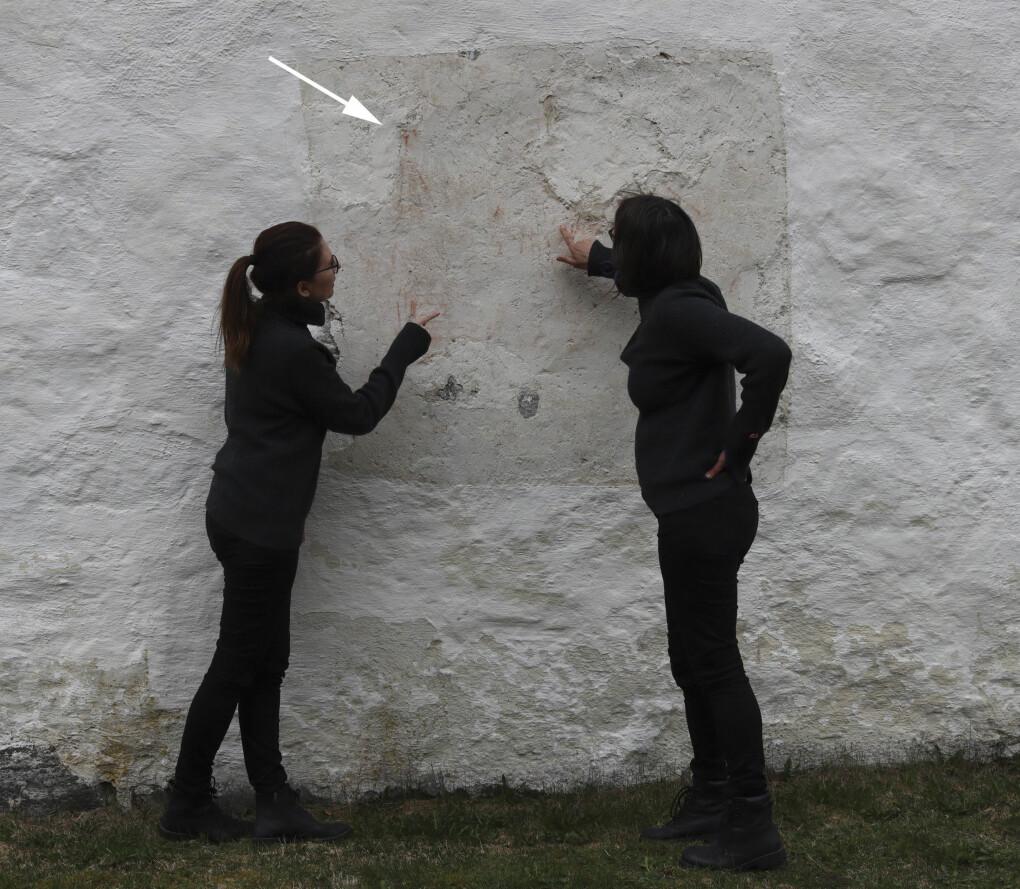 Elisabeth (t. v.) og Susanne undersøker malingsrester på Eidfjord gamle kirkes nordvegg. Man kan så vidt se at det var malt et skip med rødkritt her. Pilen viser en av mastene. Hvorfor finner vi så mange skip i kirkene? Hva kan de ha betydd?