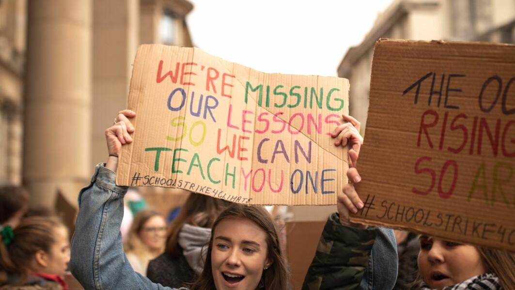 Elever i klimastreik krevde handling for miljøet. Her holder en ung person en plakat om at foreldre og lærere kan lære noe av dem