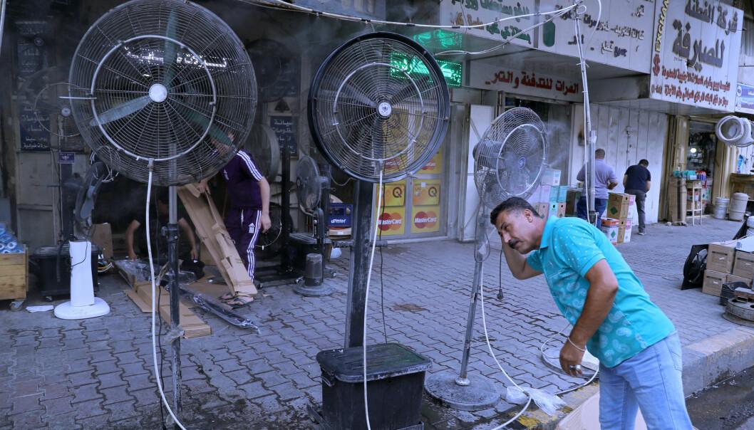 En mann kjøler seg ned med en vifte i Bagdad, der myndighetene har gitt befolkningen fri på grunn av en hetebølge.