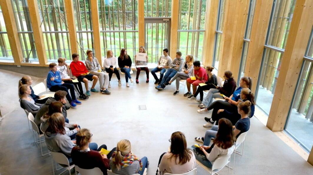 Elever sitter i ring i Hegnhuset på Utøya som del av et undervisningsopplegg.