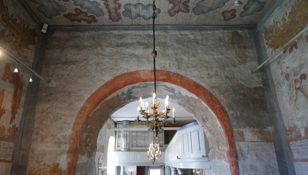 Det er ikke lett å få øye på Demonveggen, som befinner seg i koret i Sauherad kirke. Kalkmaleriene dekker hele veggen over korbuen.