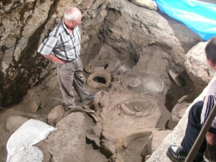 Arkeolog Levon Petrosyan (til venstre) studerer funnene i Areni-hulen. Hans venstre fot peker mot vinpressen, der druene trolig ble tråkket for 6100 år siden. Foto: Hans Barnard, UCLA.