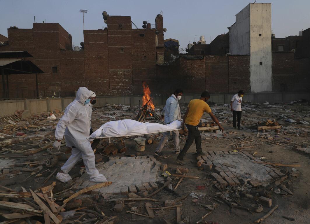 Familiemedlemmer og frivillige bærer et koronaoffer i New Delhi i India.