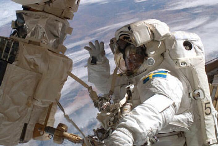 Christer Fuglesang vinker til kameraet mens han er på romvandring utenfor den internasjonale romstasjonen.Foto: NASA.