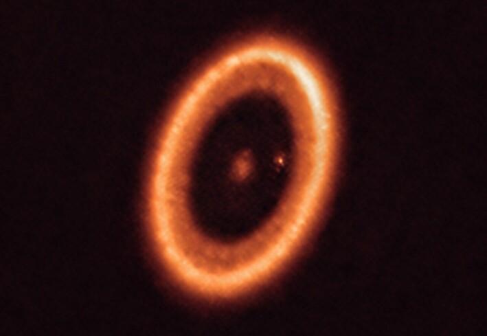 Bildet viser hele det fremmede solsystemet, med stjernen i midten. Rundt ser vi skiven med gass og støv som omgir stjernen. Den lille lysende prikken er en planet. Den har samlet opp det meste av gass og støv i området inn mot stjernen. Derfor er det blitt en tom, sort ring i skiven.