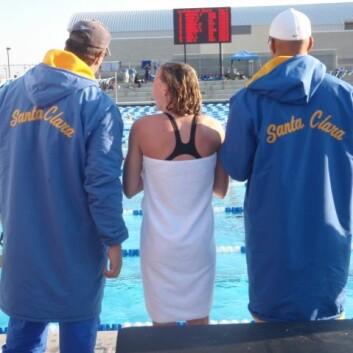 En svømmer med sine trenere på et svømmestevne. (Foto: NIH)