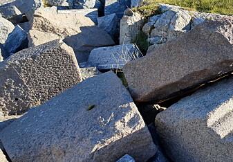 Etter rivingen av tårnets øverste del, ble steinblokkene liggende igjen rundt fyret. Den profilerte rosa blokken i forkant viser at av etasjeskillene som ble murt opp av granitt fra Oslo-området.