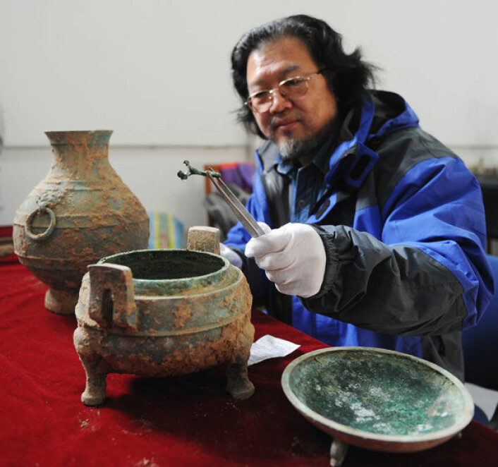 Arkeolog Liu Daiyun med gryte funnet i en 2400 år gammel grav ved Kinas gamle hovedstad Xian. Gryta inneholder dyrebein med irrgrønn patina. På bildet sees også en bronsekrukke som inneholdt en væske som kan være vin. (Foto: Zhai Xiaoxue/Xinhua/Photoshot)