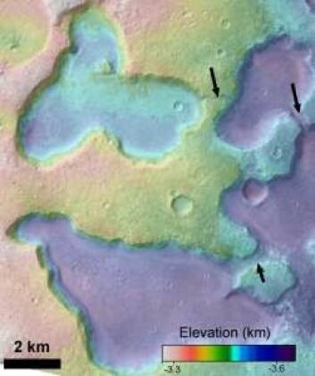 På dette bildet, med kunstige farger som angir høyden på Mars-overflaten, er tre kanaler mellom de gamle sjøene markert med piler. (Foto: NASA)
