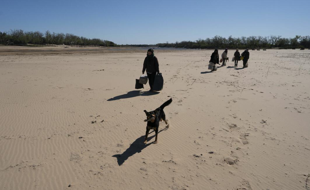 Innbyggerne i en fiskelandsby bærer varer over et delta ved elven Gamle Paraná. Tørke gjør at mange landsbyer ikke lenger kan nås med båt.