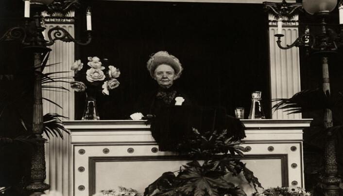 Da vi får allmenn stemmerett for kvinner i 1913, står kvinnesaksforkjemper Fredrikke Marie Qvam på scenen i den internasjonale kvinnestemmeretts allianse i Budapest og sier «Follow us, the Norwegian example.» Her avbildet på en talerstol.