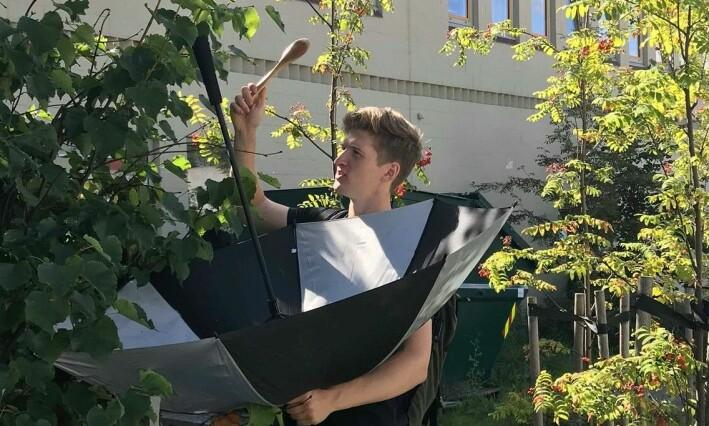 Johannes Lande Nyborg jaktar på småkryp i Sogndal sentrum med utradisjonelle verktøy: paraply og sleiv. Foto: Amalie Svendsen.