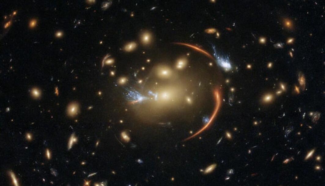På bildet ser du en hel samling av galakser. Til sammen er de så tunge at de bøyer lyset. Dette gjør at galaksene lager et slags forstørrelsesglass som forstørrer det som ligger bak. Slik har forskere kunnet se galakser som ligger mye, mye lengre unna. Her ser du den døde galaksen forstørret i midten av bildet.