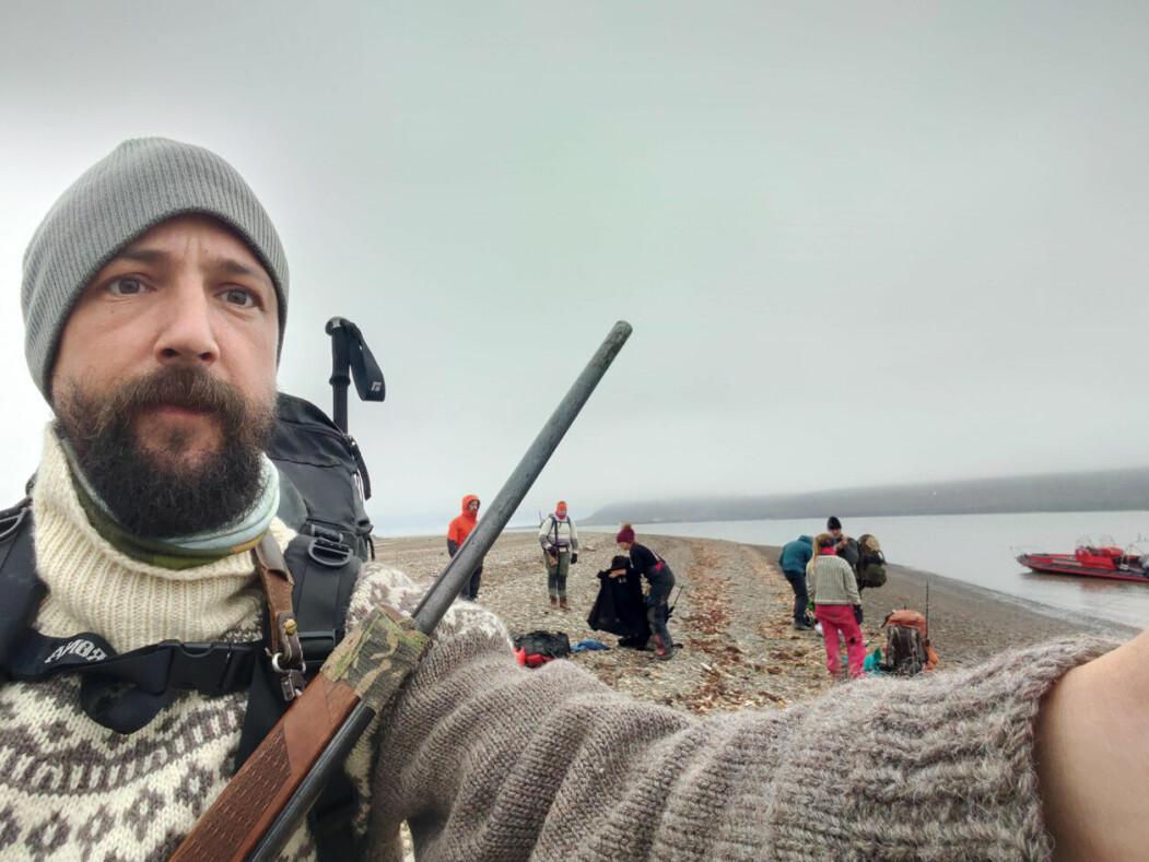 Selfie av prosjektleiar Sam Steyaert med felt-teamet i bakgrunnen. Bilete er tatt i Hiorthhamn medan dei ventar på båtskyss attende til Longyearbyen etter end arbeidsdag.