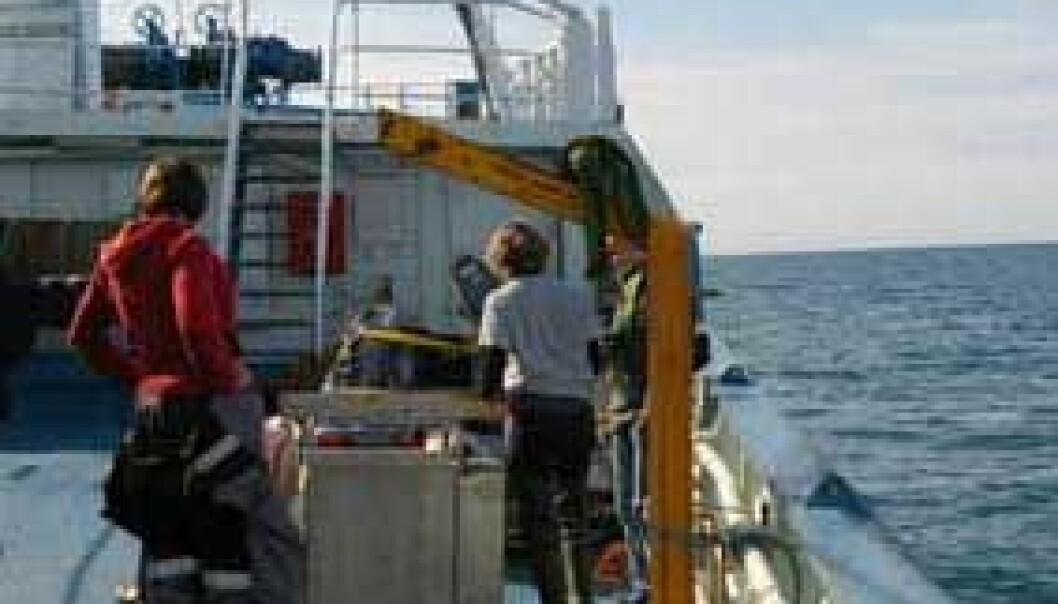 Noen av forskerne gjør klar et apparat som skal brukes til å ta prøver av plankton med, idet vi nærmer oss munningen av Isfjorden. (Foto: Bjørnar Kjensli)