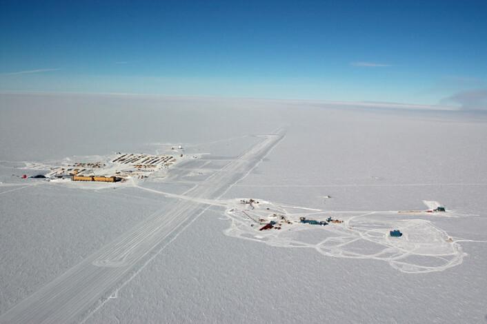 Luftfoto av Scott/Amundsen-basen til høyre og IceCube til venstre, med rullebanen i midten. (Foto: Forest Banks, NSF)