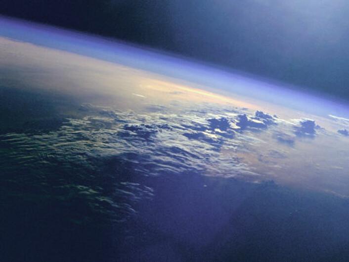 Jordas atmosfære sett fra verdensrommet. Bitte små partikler kan bli oppe i stratosfæren i flere år før de daler ned på jorda. (Foto: NASA, se nasas egen beskrivelse her)