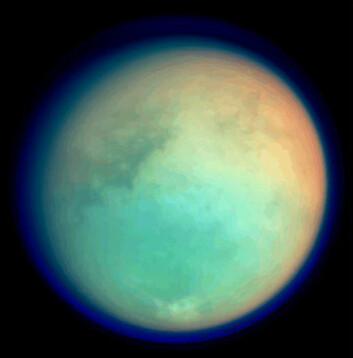 """Bildet viser Titan i ultrafiolette og infrarøde bølgelengder, men fargene er falske. Rødt og grønt representerer infrarøde bølgelengder og viser områder der atmosfærisk metan absorberer lys. Fargene viser en lysere (rødere) nordlig halvkule). Blått representerer ultrafiolette bølgelengder og viser den høye atmosfæren og lagene med dis. Oppløsningen er 6,4 kilometer per piksel."""