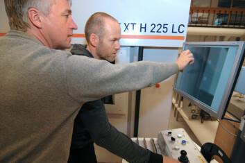 Jan Bill og Øistein Johnsen studerer de første CT-bildene av en mer enn 1000 år gammel spade fra Oseberg-haugen. (Foto: NGI)