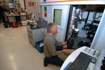 Professor Jan Bill fester to mer enn 1000 år gamle spader til et spesialkonstruert stativ som skal plasseres inne i kammeret i NGIs CT-scanner. (Foto: NGI)