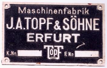 """""""I motsetning til sin hovedkonkurrent, selskapet Kori, valgte Topf & Söhne å sette logoen sin på likbrenningsovnene de leverte til SS. Det gjorde arbeidet lett for etterforskerne. Totalt ble fire av selskapets ledere sendt til arbeidsleire i Sibir etter krigen, og bare to av dem overlevde. Deler av selskapet var i drift helt frem til 1996. (Foto: Sammlung Gedenkstätte Buchenwald/Peter Hansen)"""