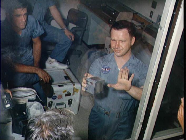 """""""Da Terry Slezak, en av fototeknikerne på jorda, skulle ta ut filmkassetten av et av Hasselbladkameraene fikk han hånda full av månestøv. Dette var første gang noen andre enn astronautene hadde vært borti støvet, og ingen visste helt hvordan man skulle reagere. På dette bildet sitter fortsatt astronautene i karantene fordi man var redde for at de kunne ha tatt med seg noe utenomjordisk smitte hjem fra verdensrommet. (Foto: NASA)"""""""