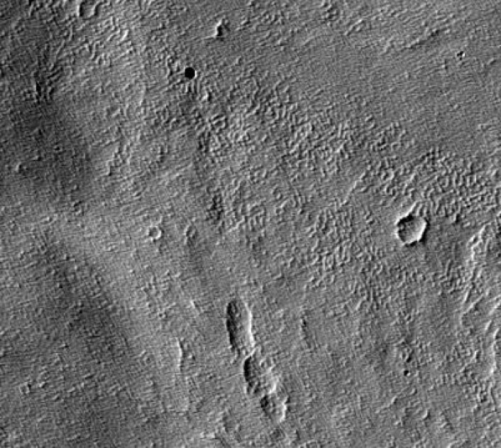 Øverst til venstre sees et lavarør, en munning på en gammel vulkan som kan romme en hule der framtidige marskolonister kan søke tilflukt. (Foto: HiRISE-sonden, NASA)