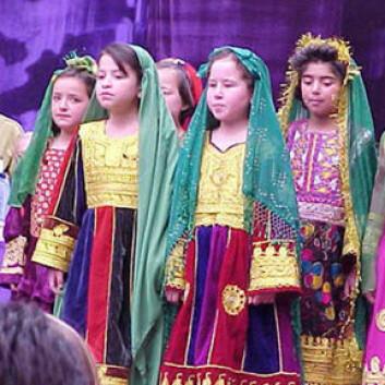 """""""Afghanske småjenter synger i tradisjonelle klesdrakter. (Foto: USAID, Wikimedia Commons)"""""""