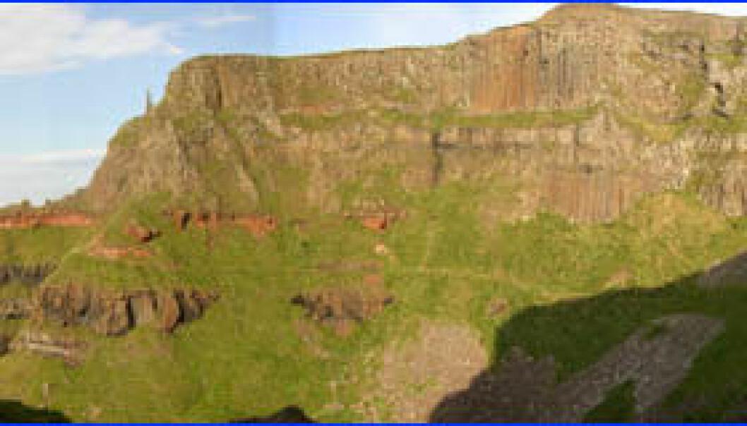"""""""Landskapet ved Gigant's Causeway i Nord-Irland ble dannet av flere vulkanske utbrudd for over 60 milloner år siden. Tykke lag med lava ble avsatt. Lagrekken viser også at det har vært roligere tider. Det røde laget er lateritt, et jordsmonn som er utviklet i toppen av basalten. Over dette har det kommet flere nye lag med basalt etter hvert som vulkanismen blusset opp igjen."""""""