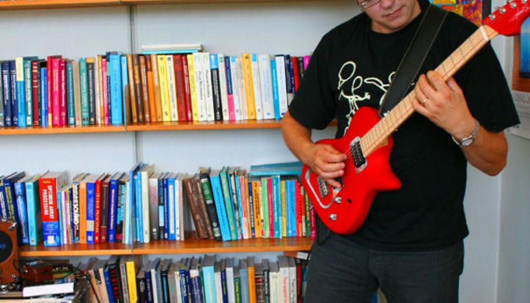 """""""Musikk og fysikk er uløselig knyttet til hverandre. Alfred Hanssen med sin ergonomiske gitar foran fagbøkene."""""""