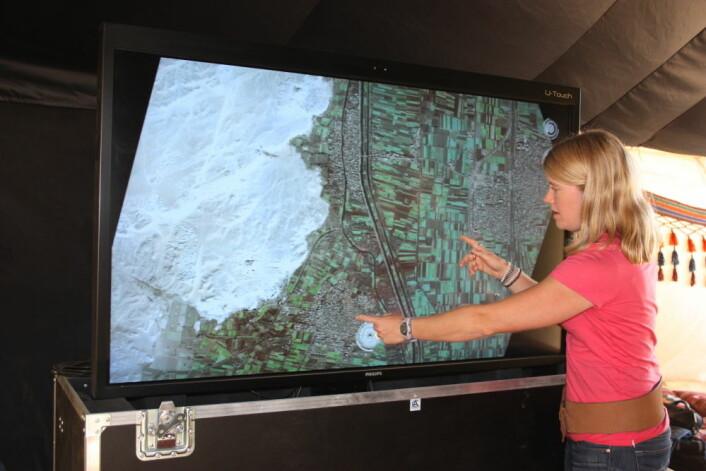 Sarah Parcak foran ett av satellittbildene. (Foto: UAB)