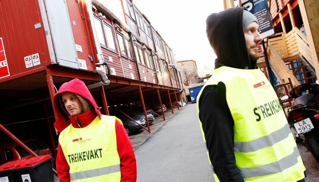 Morten Jensen (t.v.) og Kristoffer Hansen fra Veidekke var streikevakter i Teatergata i Oslo tirsdag denne uken. Rundt 19.000 ansatte gikk ut i streik etter at meklingen mellom Fellesforbundet og Byggenæringens Landsforening ikke førte fram. (Foto: Erlend Aas/Scanpix)